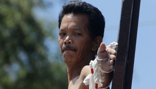 Renato Cunanan, 48, who portrays Jesus Christ, looks at the nail in his palm on a wooden cross during a Good Friday crucifixion re-enactment in San Juan village, Pampanga province, north of Manila March 29, 2013. The Roman Catholic church frowns on the gory spectacle held in the Philippine village of Cutud every Good Friday but that does nothing to deter the faithful from emulating the suffering of Christ and taking a painful route to penitents. Holy Week is celebrated in many Christian traditions during the week before Easter.  REUTERS/Romeo Ranoco (PHILIPPINES - Tags: RELIGION SOCIETY)