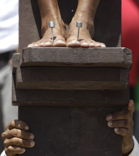 A Filipino penitent has his foot nailed to the cross during Good Friday rituals on March 29, 2013 at San Jose, Pampanga province, northern Philippines. Several Filipino devotees had themselves nailed to crosses Friday to remember Jesus Christ's suffering and death, an annual rite rejected by church leaders in this predominantly Roman Catholic country. (AP Photo/Aaron Favila)