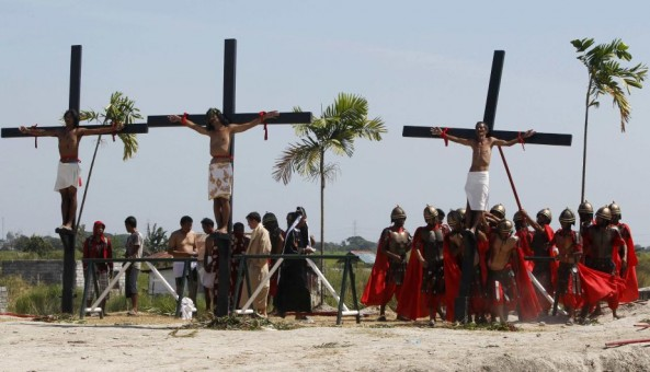 Penitents hang on wooden crosses after they were nailed to them during a Good Friday crucifixion re-enactment in San Pedro Cutud town, Pampanga province, north of Manila March 29, 2013. About two dozen Filipinos were nailed to crosses on Good Friday in an extreme display of devotion that the Catholic church looks down upon as a form of folk religion but appears powerless to stop. Holy Week is celebrated in many Christian traditions during the week before Easter.  REUTERS/Romeo Ranoco (PHILIPPINES - Tags: RELIGION SOCIETY)